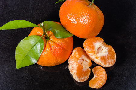 Ripe tangelos with green leaves and fruit sections
