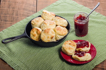 Cast iron skillet of fresh biscuits or scones with jam or jelly