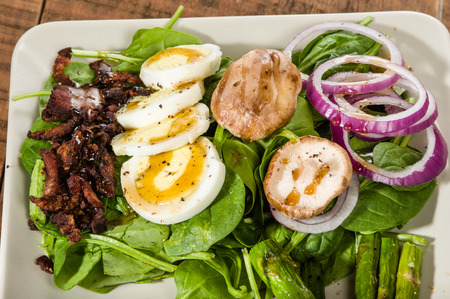 Fresh spinach salad with bacon bits and egg photo
