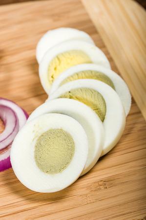 boiled egg: Fresh hard boiled egg sliced on a bamboo cutting board