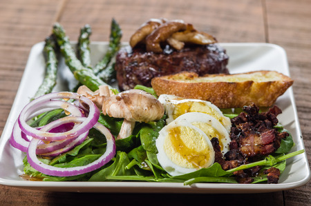 Steak and spinach salad with onion rings and mushrooms photo
