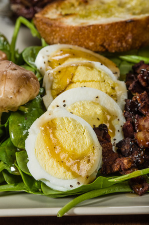 Spinach and egg salad with sliced hard boiled eggs photo