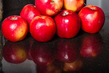 granite kitchen: Group of red apples on a black granite kitchen counter