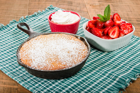 cast iron red: Cast iron skillet baked cake with bowl of red strawberries