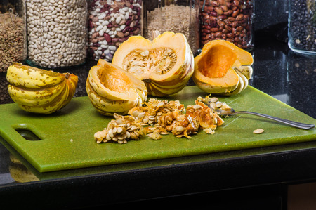 removed: Winter acorn squash hollowed and seeds removed on cutting board Stock Photo