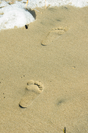 Footsteps on a lonely beach in the sand