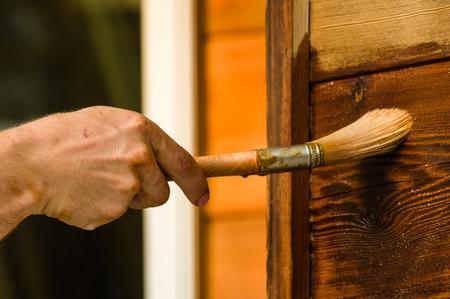 pintor: Pintor con el cepillo de aplicar el acabado de revestimiento de madera