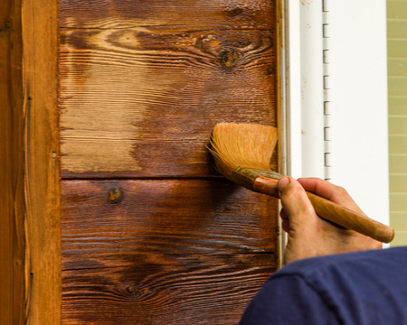 staining: Painter with brush applying finish to wood siding