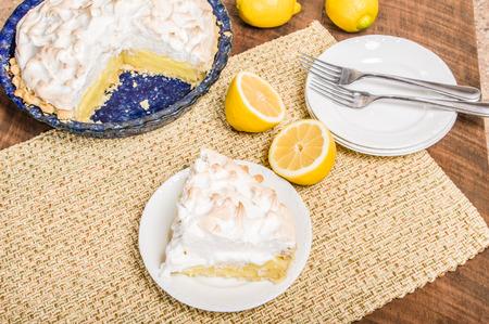Slice of lemon meringue pie on white serving plate