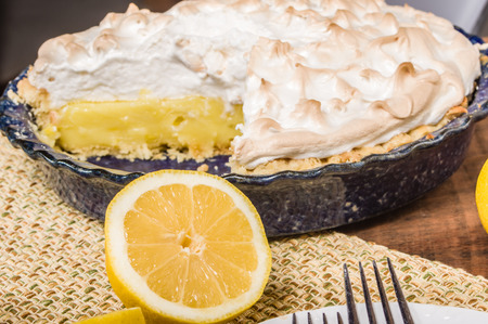 Homemade lemon meringue pie with cut lemon fruit