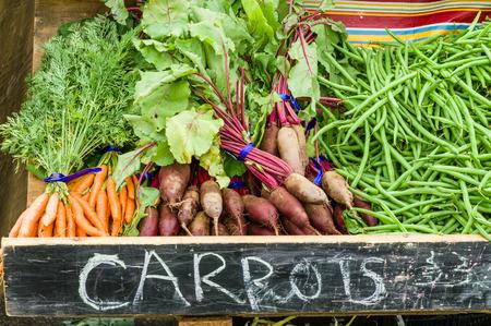 snap bean: Display of carrots and beets at the farm market Stock Photo