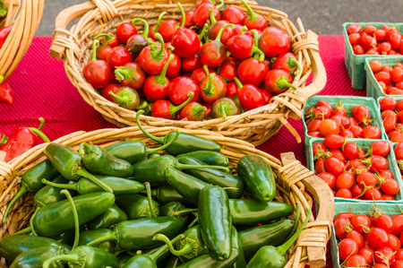 chiles picantes: Baskets of hot peppers and cherry tomatoes at the market
