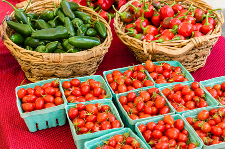 hot peppers: Baskets of hot peppers and cherry tomatoes at the market