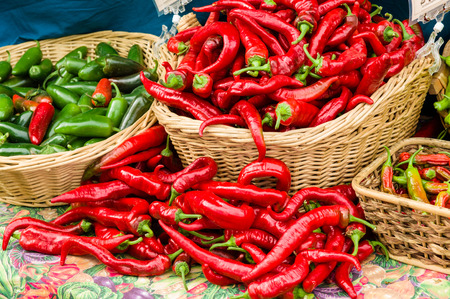 Red hot peppers in baskets displayed at the farm market Banco de Imagens