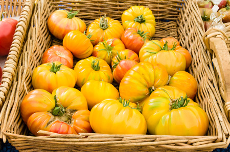 heirloom: Basket of ripe heirloom tomatoes at the farm market