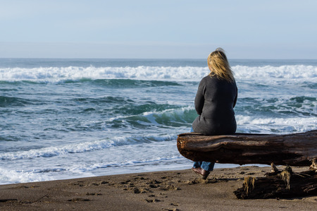 woodcutting: Woman sitting on a log staring out to sea Stock Photo