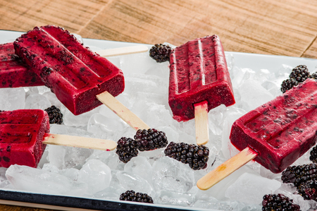 Frozen blackberry pops with berries on tray of ice