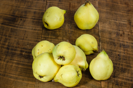 quinces: Group of fresh picked quince fruit on a wooden table Stock Photo