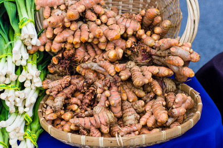 Fresh tumeric root in a basket at the market