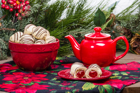 christmastide: Holiday themed tea pot and filled Christmas cookies Stock Photo