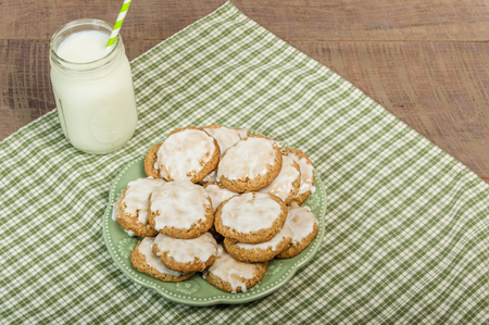 Baked cookies with white icing and milk