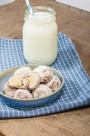 Cookies rolled in powdered sugar with milk
