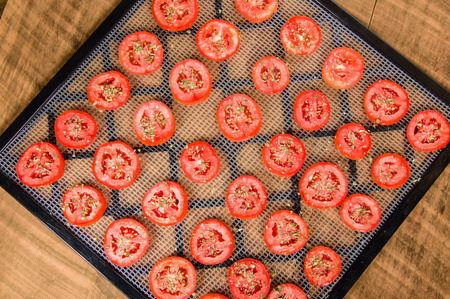 legumbres secas: Slices of seasoned tomatoes on a drying rack for preserving