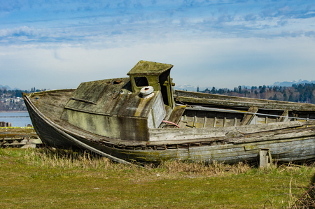 A wooden boat long abandoned sitting on the shore Stock Photo