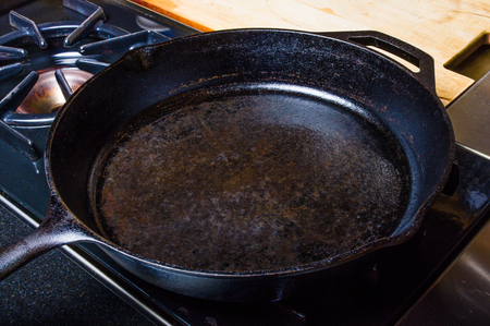 Cast iron skillet on stove oild and ready to use Stock Photo