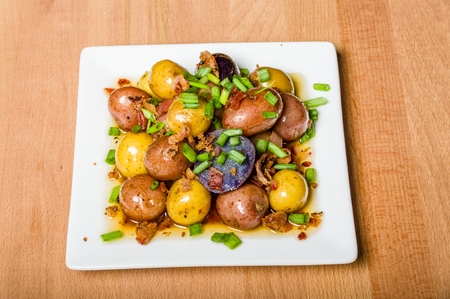 Fresh new potatoes boiled and dressed to serve on a white plate