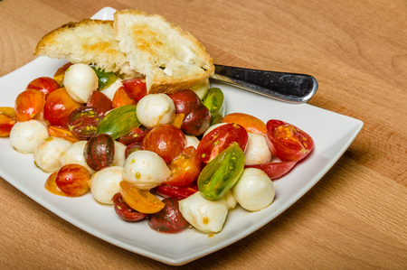 harvested: Fresh heirloom tomatoes with cheese served with bread on plate Stock Photo