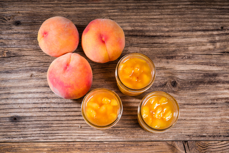 harvested: Ripe yellow peaches and jars of preserves or pie filling