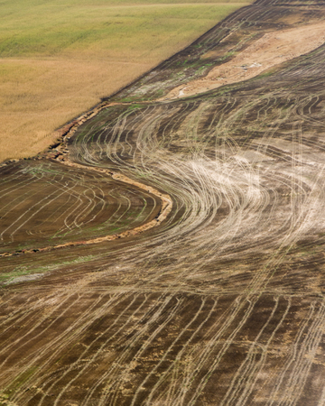 harvested: Aerial view of brown fallow cropland that has been harvested