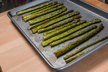 Gebakken gekruide asperge op bakplaat met kruiden en olijfolie
