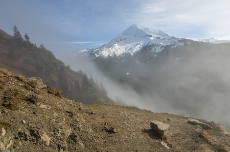 Fog rolling over the pass near snow capped Mt Hood Stock Photo