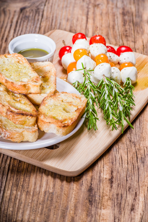 Tomato cheese and bread appetizers on rosemary skewers