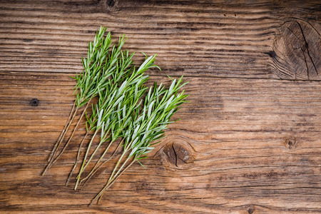 Stems of rosemary herb for skewers on a wooden table