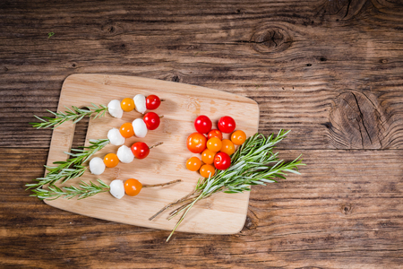 Tomatoes and cheese balls on rosemary skewers Banco de Imagens