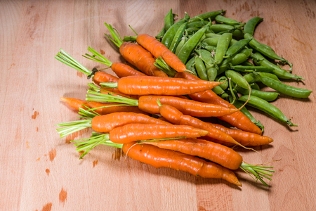 Fresh peas and carrots from the garden being prepared