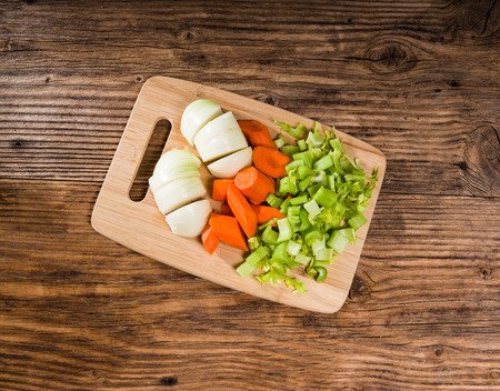 Vegetable mirepoix of carrots, celery and onions  on a cutting board Banco de Imagens