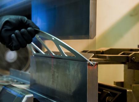 bending: operator bending metal sheet by sheet bending machine Stock Photo