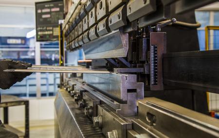 worker operating metal press machine at workshop. 스톡 콘텐츠