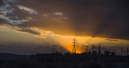 sunset under the high-voltage tower in the background Stock Photo
