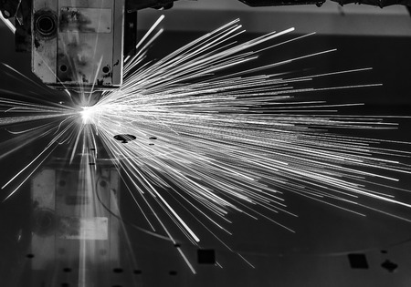 Industrial Laser cutting processing manufacture technology of flat sheet metal steel material with sparks laser cut metal splashes Stock Photo