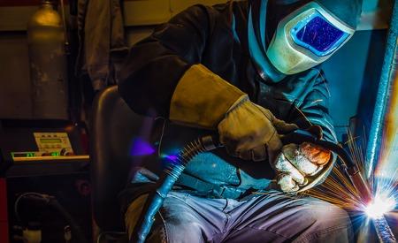 improvisation: welder, craftsman, erecting technical steel Industrial steel welder in factory
