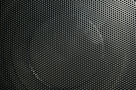 The speaker of a musical column hidden behind a grid with a pattern of rhythmically arranged holes Grid music speakers.