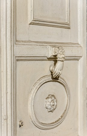 Old carved white door. old palace white wooden door and white metal knocker