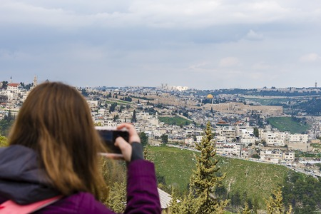 Woman taking photograph with smartphone at enjoying view of Jerusalem Banco de Imagens
