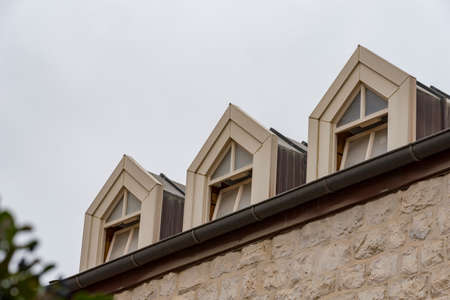 Roof with three beautiful white dormer windows. Ancient round dormer windows in rooftop. Symmetrical view on roof with three garret windows Three white windows rooftop.