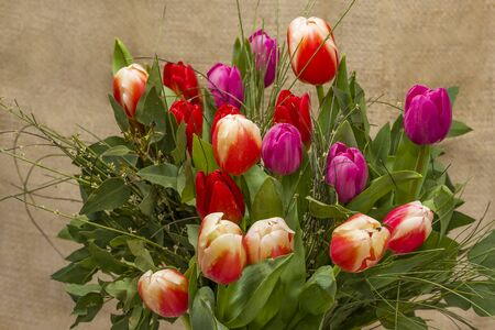 Bright spring flowers tulips bouquet on the table directly above view, colorful pink, red and yellow blooming tulips in vibrant colors Bouquet of tulips red-pink, red-yellow.